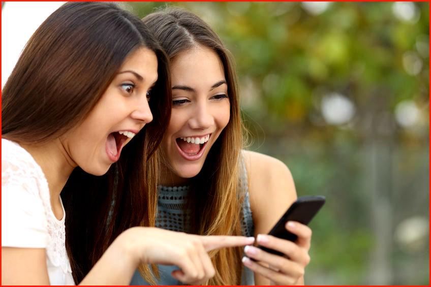 Девочки смотрят в телефон и смеются